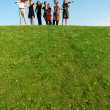 Stock Photo: Group of musicians play violins on hill against sky