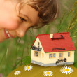 Child looks on model of house outdoor — Stock Photo