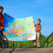 Man with  boy they hold in hands  expanded map outdoor - Stock Photo