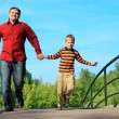 Man and boy run on bridge in summer - Stock Photo
