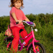 Young curly girl biker rests in the field — Stock Photo