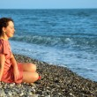 Stock Photo: Young woman sits ashore of sea
