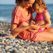 Mother with daughter sits on seacoast — Stock Photo