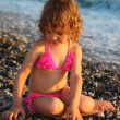 Little girl sits on beach — Stock Photo