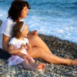 Stock Photo: Mother with daughter sits on seacoast