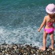 Little girl stands on beach, rear view — Stock Photo