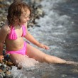 Stock Photo: Little girl sits ashore in waves