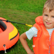 Boy and inflatable boat on lawn — Stock Photo