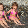 Two little girls sit ashore in water — Foto de Stock
