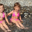 Two little girls sit ashore in water — Stockfoto
