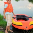 Boy and inflatable boat ashore — Stock Photo