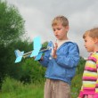 Little girl and boy with toy airplane in hands outdoor — Stock Photo #7428659