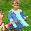 Little girl and boy with toy airplane in hands outdoor — Stock Photo #7428661