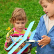 Little girl and boy with toy airplane in hands outdoor — Stock Photo #7428664