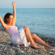 Stock Photo: Young woman sits ashore of sea with rised hands