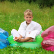 Karate boy sits in inflatable armchair on lawn — Stock Photo #7428691