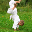 Karate boy does handstand on lawn — Stock Photo #7428697