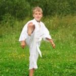 Karate boy kick a leg outdoor — Stock Photo #7428711