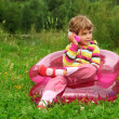 Little girl sits talks by toy phone in inflatable armchair on l — Stock Photo