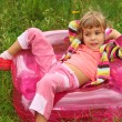 Little girl sits talks by toy phone in inflatable armchair on l — Stock Photo #7428727
