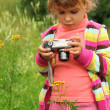 Little girl with photo camera outdoor — Stock Photo