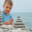 Boy and stone stacks on pebble beach — Stock Photo