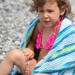 Little girl sits on pebble - Stock Photo