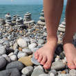 Two legs and stone stacks on pebble beach — Stock Photo