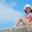 Little girl sits on rock against sky — Stock Photo #7428813