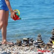 Child waters from watering can stone stacks on beach — Stock Photo