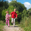 Two children run on path in summer — Stock Photo