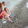 Happy family with little girl sitting on stony beach, Looking af - Stock Photo