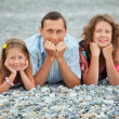 Happy family with little girl lying on stony beach, focus on fat — Stock Photo