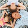 Happy family with little girl lying on stony beach, Concerning w — Stock Photo #7428952