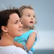 Beautiful woman protects little girl from wind on seacoast — Stock Photo #7429003