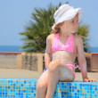Stock Photo: Pretty little girl smeared with cream for sunburn wets feet wate