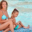 Beautiful woman with little girl sit near in pool — Stock Photo