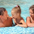 Happy family with little girl bathe in pool - Stock Photo