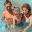 Happy family with little girl plays in pool — Stock Photo