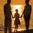 Silhouettes against glossing sea — Stock Photo