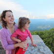 Mother and daughter look on mountain from balcony — Stock Photo #7429136