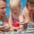 Closeup parents with child on sea coast and  pyramid of stones — Stok fotoğraf
