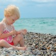 Child sits on pebble beach — Stock Photo