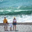 Parents with child stand on seacoast,  rear view — Stock Photo
