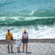 Stock Photo: Parents with child stand on seacoast, rear view