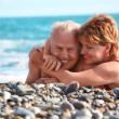 Happy aged pair lie on pebble beach — Stock Photo