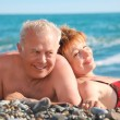 Happy aged pair lie on pebble beach — Stock Photo #7429273