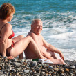 Aged pair sit on pebble beach — Stock Photo #7429274