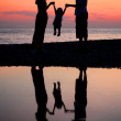 Silhouettes of parents with child against sea decline — Stock Photo