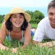 Young couple lies on grass — Stock Photo #7429294